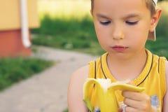 Sund pys som äter bananen Den lyckliga ungen tycker om att äta ny frukt Arkivfoton