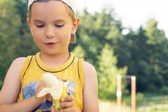 Sund pys som äter bananen Den lyckliga ungen tycker om att äta ny frukt Royaltyfria Foton