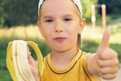 Sund pys som äter bananen Den lyckliga ungen tycker om att äta ny frukt och uppvisning tummar upp Royaltyfria Foton