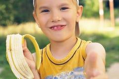 Sund pys som äter bananen Den lyckliga ungen tycker om att äta ny frukt och uppvisning tummar upp Arkivfoto