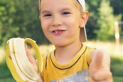 Sund pys som äter bananen Den lyckliga ungen tycker om att äta ny frukt och uppvisning tummar upp Royaltyfri Bild