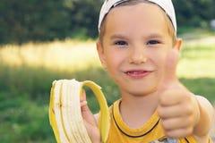 Sund pys som äter bananen som ser kameran med den lyckliga framsidan som visar upp tummar Den lyckliga ungen tycker om att äta so Royaltyfri Fotografi