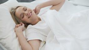 Sund sömn på den ortopediska madrassen, lycklig tonårs- flicka som vaknar upp med leende lager videofilmer