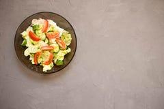 sund sallad, grönsak, tomater, gurkor, isberg, bestick, grå bakgrund Top beskådar kopiera avstånd royaltyfri foto