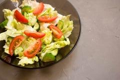 sund sallad, grönsak, tomater, gurkor, isberg, bestick, grå bakgrund Top beskådar kopiera avstånd arkivfoto