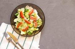 sund sallad, grönsak, tomater, gurkor, isberg, bestick, kökshandduk, grå bakgrund kopiera avstånd vegetarian arkivfoto