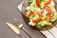 sund sallad, grönsak, tomater, gurkor, isberg, bestick, kökshandduk, grå bakgrund kopiera avstånd vegetarian royaltyfria foton