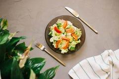 sund sallad, grönsak, tomater, gurkor, isberg, bestick, Spathiphyllum, kökshandduk, grå bakgrund royaltyfria foton