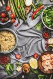 Sund sallad med sparris och lagat mat quinoafrö, förberedelse på lantlig bakgrund med olika organiska grönsaker, bästa sikt, royaltyfri foto