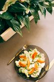 sund sallad, ny grönsak, tomater, gurkor, isberg, bestick, Spathiphyllum, grå bakgrund Top beskådar arkivbild