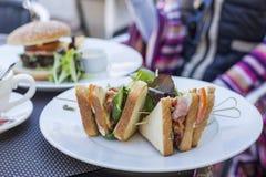 Sund sandvich med sallad som tjänas som på tabellen Hamburgare på den vita plattan Arkivbilder