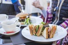 Sund sandvich med sallad som tjänas som på tabellen Hamburgare på den vita plattan Royaltyfri Foto