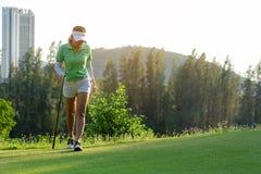 Sund sport Asiatisk sportig kvinna för golfare som går för att koppla av på farleden för den satta golfbollen på den gröna golfaf arkivfoton