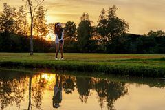 sund sport Asiatiska sportiga chiper för kvinnagolfarespelare och att svänga golf på den gröna solnedgångaftontiden arkivbilder
