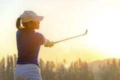sund sport Den asiatiska sportiga kvinnagolfarespelaren som g?r golfgungautslagsplatsen av p? den gr?na aftontiden, ?var hon f?rm royaltyfria bilder