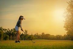Sund sport Den asiatiska sportiga kvinnagolfspelaren som gör golfgungautslagsplatsen av på den gröna solnedgångaftontiden, gör ho arkivfoton