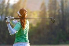 Sund sport Den asiatiska sportiga kvinnagolfspelaren som g?r golfgungautslagsplatsen av p? den gr?na solnedg?ngaftontiden, g?r ho fotografering för bildbyråer
