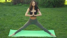 Sund sportlivsstil Parkerar praktiserande yoga för kvinna utomhus i arkivfilmer