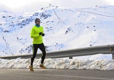 Sund sportmanspring på asfaltvägen på snöberg i hård genomkörare för slingalöpare i vinter arkivfoton
