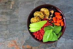 Sund strikt vegetarianbuddha bunke med falafels, betaquinoaen, avokadot och grönsaker, bästa sikt på en mörkerstenbakgrund royaltyfri bild