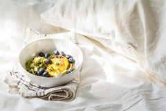 Sund strikt vegetarianfrukost i s?ng Granola med avokadot, superfoods, b?r och frukter i en vit bunke royaltyfri foto