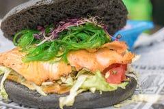 Sund svart hamburgare med fisken och ny sallad som ett smakligt mellanmål royaltyfri bild