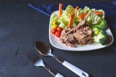Sund tonfisk och gr?nsaker i en platta p? tabellen royaltyfria foton