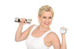 Sund ung blond kvinna för attraktiv lycklig passform som utarbetar med dumma Klocka vikter Arkivbild
