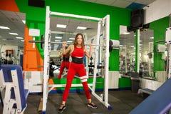 Sund ung kvinna med skivstången som utarbetar den kvinnliga idrottsman nen som övar med tunga vikter på idrottshallen arkivfoton
