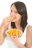 Sund ung kvinna som äter en platta av nya orange segment Arkivbild