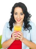 Sund ung kvinna som dricker stort exponeringsglas av ny orange fruktsaft Royaltyfri Foto