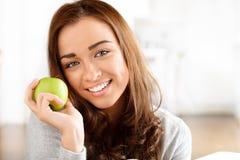 Sund ung kvinna som rymmer det gröna äpplet Fotografering för Bildbyråer