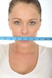 Sund ung kvinna som rymmer en måttband över hennes mun arkivfoto