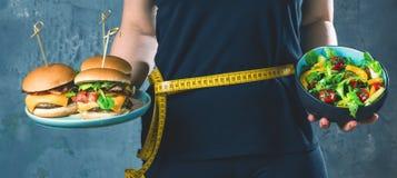 Sund ung kvinna som ser sunda och sjukliga plattor av mat som försöker att göra det högra valet royaltyfri bild