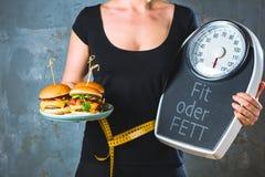 Sund ung kvinna som ser sunda och sjukliga plattor av mat som försöker att göra det högra valet royaltyfri fotografi