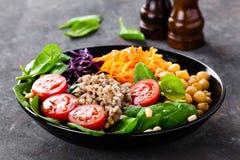 Sund vegetarisk maträtt med bovete- och grönsaksallad av kikärten, grönkål, morot, nya tomater, spenatsidor och att sörja muttrar royaltyfri foto