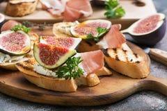 Sunda bruschettas med bröd, gräddost, prosciuttoen, fikonträd och persilja på lantlig bakgrund Selektivt fokusera arkivfoto