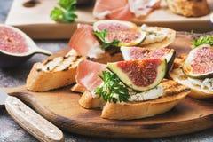 Sunda bruschettas med bröd, gräddost, prosciuttoen, fikonträd och persilja på lantlig bakgrund Selektivt fokusera arkivfoton