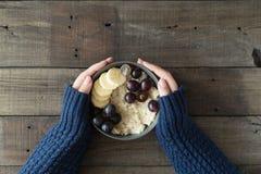 Sunda frukostgrå färger bowlar med havremjölhavregröt och frukter i händer för kvinna` s Banta matbegreppet royaltyfri foto