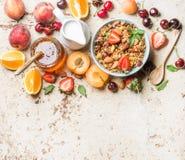 Sunda frukostingredienser Havregranola i bunke med muttrar, jordgubbe och mintkaramell, mjölkar i tillbringaren, honung i den gla royaltyfri bild
