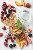 Sunda frukostingredienser Havregranola i den glass kruset med persikan, jordgubbe, söta körsbär, björnbär på ljus Royaltyfri Bild