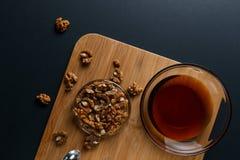 Sunda frukostingredienser: honung valn?tter p? en m?rk bakgrund arkivfoton