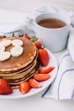 Sunda frukostpannkakor med jordgubbar, bananer, kopp av svart te på vit bakgrund med den vita handduken Arkivfoto
