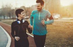 Sunda idrotts- par som tillsammans joggar och kör som är utomhus- Royaltyfri Bild