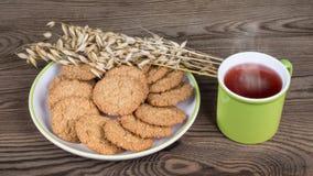 Sunda kakor och rånar med varmt te på en träbakgrund royaltyfri foto
