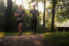 Sunda konditionpar som utomhus joggar Arkivfoto