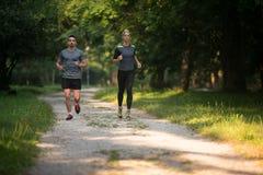 Sunda konditionpar som utomhus joggar Royaltyfri Fotografi