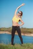 Sunda livsstil- och sportbegrepp Kvinnan i trendig sportswear och solglasögon gör övning på naturen Flicka på solig da Royaltyfria Foton