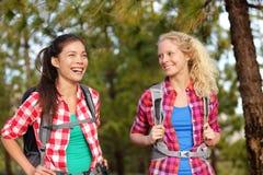 Sunda livsstilkvinnor som skrattar att fotvandra i skog Arkivfoto
