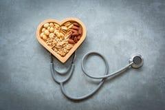sunda matar Blandade muttrar i hjärtaform och stetoskopet med muttrar för bantar på en konkret bakgrund Olika sorter av smakligt  arkivfoto